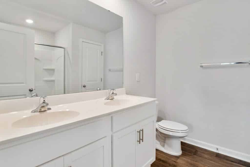 White bathroom with vanity and toilet